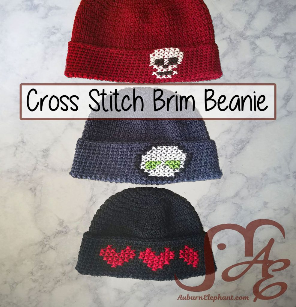 Three crochet beanies with cross stitch designs on brim