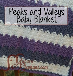 Hanging crochet blanket in purple, grey, and white.
