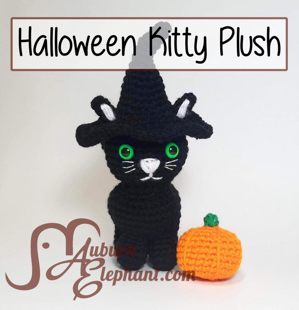 Black Kitty Plush wearing black Halloween Witch Hat next to orange pumpkin.