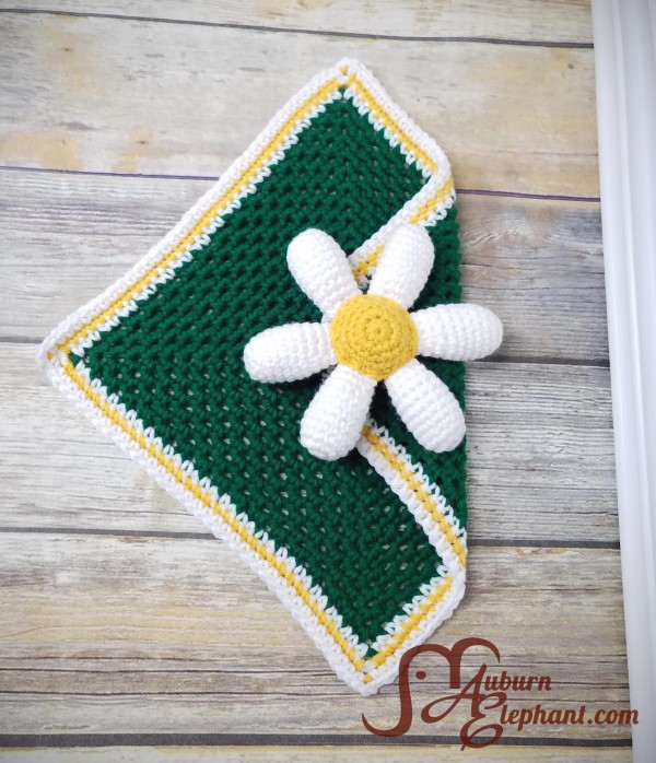 White daisy petals with a yellow center folded to the middle of a small green square crochet blanket.