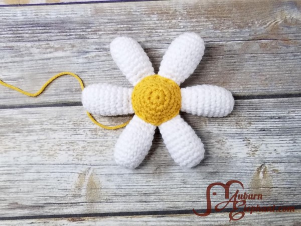 Six crocheted white daisy petals with a yellow center form the flower shape.