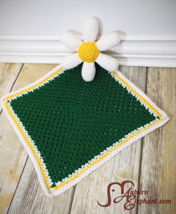 Crocheted white daisy petals with a yellow center connected to the corner of a green square crochet blanket.