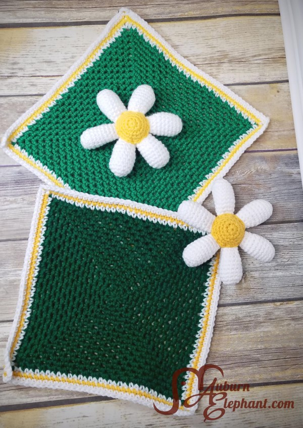 Two crocheted loveys with white daisy petals with yellow centers connected to small green square crochet blankets.