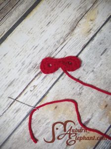 A red crocheted super hero mask attached to a sewing needle.